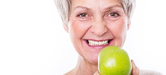Older woman with implant denture holding an apple.