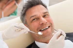 man smiling during a dental checkup